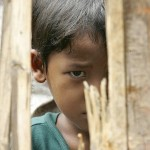 A karen boy looks through bamboo at Tham